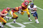 Shane Vereen #34 of the California Golden Bears is chased by Armond Armstead #94, Shareece Wright #24 and Nick Perry #8 of the USC Trojans during the first quarter at Los Angeles Memorial Coliseum on October 16, 2010 in Los Angeles, California.