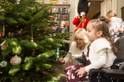 Maya Czerminska helps Camilla, Duchess of Cornwall decorate a Christmas Tree during a reception at Clarence House hosted by the Duchess of Cornwall, for youngsters and their carers from Helen and Douglas House on December 11, 2013 in London, England.