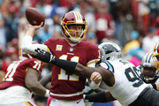 Quarterback Alex Smith #11 of the Washington Redskins is hit as he throws by defensive tackle Kawann Short #99 of the Carolina Panthers in the first quarter at FedExField on October 14, 2018 in Landover, Maryland.