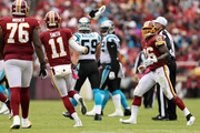 Quarterback Alex Smith #11 of the Washington Redskins throws running back Adrian Peterson #26 of the Washington Redskins his shoe in the second quarter against the Carolina Panthers at FedExField on October 14, 2018 in Landover, Maryland.