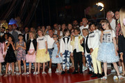 Fashion designers, founders and owners of Dsquared2 Dan Caten and Dean Caten pose with models at the Caten Hight School Prom DSquared2 as a part of Pitti Bimbo Kids Fashion Week at Palamattioli on June 21, 2018 in Florence, Italy.