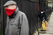 Two men wearing face protection watch as members of the Coldstream Guards prepare to march to Buckingham Palace on the day that Queen Elizabeth II is set to move to Windsor Palace in a bid to avoid the COVID-19 coronavirus pandemic on March 18, 2020 in London, England.