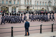 A man watches the Changing of the Guard ceremony outside Buckingham Palace on the day that Queen Elizabeth II is set to move to Windsor Palace in a bid to avoid the COVID-19 coronavirus pandemic on March 18, 2020 in London, England.