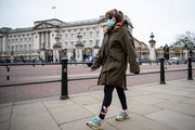 A woman wearing a face mask walks past Buckingham Palace on the day that Queen Elizabeth II is set to move to Windsor Palace in a bid to avoid the COVID-19 coronavirus pandemic on March 18, 2020 in London, England.