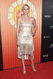 Charlize Theron polished off her look with strappy gold heels.