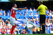 Referee Mike Dean prepares to show the second yellow card to  Santi Cazorla of Arsenal during the Barclays Premier League match between Chelsea and Arsenal at Stamford Bridge on September 19, 2015 in London, United Kingdom.