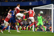 Marcos Alonso of Chelsea is pressured by Shkodran Mustafi, Sokratis Papastathopoulos and Aaron Ramsey of Arsenal during the Premier League match between Chelsea FC and Arsenal FC at Stamford Bridge on August 18, 2018 in London, United Kingdom.