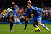 Eden Hazard (R) of Chelsea holds off the challenge of Vurnon Anita (L) of Newcastle United during the Barclays Premier League match between Cheslea and Newcastle United at Stamford Bridge on February 8, 2014 in London, England.