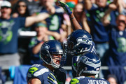 Tight end Jimmy Graham #88 (L) is congratulated by teammates after scoring a touchdown against the Chicago Bears in the fourth quarter at CenturyLink Field on September 27, 2015 in Seattle, Washington. The Seahawks defeated the Bears 26-0.