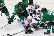 Andrew Shaw #65 and Jonathan Toews #19 of the Chicago Blackhawks skate for the puck against Jamie Benn #14 and Alex Goligoski #33 of the Dallas Stars in the third period at American Airlines Center on October 9, 2014 in Dallas, Texas.
