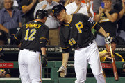 Clint Barmes #12 of the Pittsburgh Pirates celebrates with Justin Morneau #66 after scoring on a RBI double in the eighth inning against the Chicago Cubs during the game on September 12, 2013 at PNC Park in Pittsburgh, Pennsylvania.