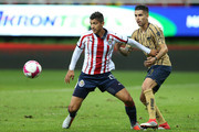 Angel Zaldivar #14 of Chivas fights for the ball with David Cabrera #07 of Pumas during the 12th round match between Chivas and Pumas UNAM as part of the Torneo Apertura 2018 Liga MX at Akron Stadium on October 6, 2018 in Zapopan, Mexico.