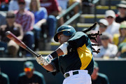Manny Ramirez #1 of the Oakland Athletics follows through on a swing against the Cincinnati Reds  during a spring training game at the Phoenix Municipal Stadium on March 10, 2012 in Phoenix, Arizona.