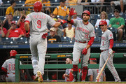 Jose Peraza #9 of the Cincinnati Reds is greeted at home plate by Joey Votto #19 and Scooter Gennett #3 after hitting a solo home run in the first inning during the game against the Pittsburgh Pirates at PNC Park on September 5, 2018 in Pittsburgh, Pennsylvania.