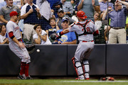 Curt Casali #38 of the Cincinnati Reds fails to catch a foul ball as Joey Votto #19 looks on in the third inning against the Milwaukee Brewers at Miller Park on September 17, 2018 in Milwaukee, Wisconsin.