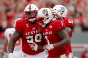 Teammates Tony Adams #50 and Jaylen Samuels #1 of the North Carolina State Wolfpack celebrate after a touchdown against the Clemson Tigers during their game at Carter Finley Stadium on November 4, 2017 in Raleigh, North Carolina.