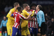 Gerard Pique (L) and Frankie De Jong (3dL) of FC Barcelona, Koke, (2ndL), Hector Herrera (3dR) and Thomas Teye Partey (R) of Atletico de Madrid argue with referee Mateu Lahoz (R) during the Liga match between Club Atletico de Madrid and FC Barcelona at Wanda Metropolitano on December 01, 2019 in Madrid, Spain.