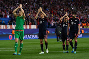 Manuel Neue, Thomas Mueller, Philipp Lahm and Javi Martinez of Bayern Munich applaud the away supporters  during the UEFA Champions League semi final first leg match between Club Atletico de Madrid and FC Bayern Muenchen at Vincente Calderon on April 27, 2016 in Madrid, Spain.