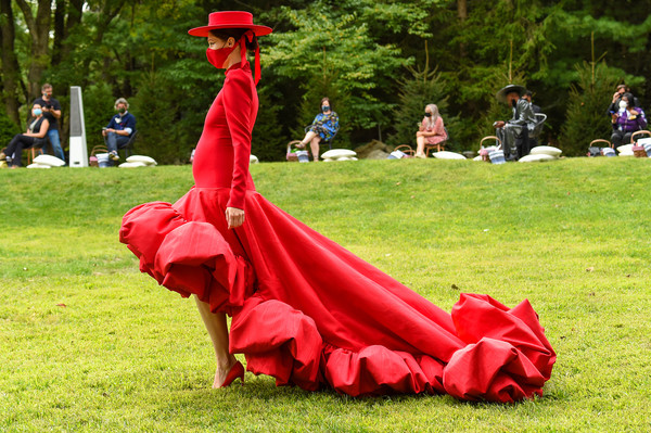 Christian Siriano Collection 37 2020 Fashion Show - Runway [red,dress,grass,outerwear,lawn,event,plant,flower,outerwear,dress,coco rocha,red,flower,tree,runway,lawn,westport,christian siriano collection 37 2020 fashion show,middle ages,lawn,flower,red,tree,outerwear,summer]