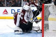 Jan Hejda #8 of the Colorado Avalanche tumbles over goalie Semyon Varlamov #1 as Varlamov holds onto the puck after making a save against the Los Angeles Kings at Staples Center on April 4, 2015 in Los Angeles, California.