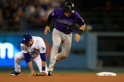 Tony Wolters #14 of the Colorado Rockies runs to third as Chase Utley #26 is unable to catch a wild throw to second by Yasmani Grandal #9 of the Los Angeles Dodgers during the eighth inning of a game at Dodger Stadium on May 21, 2018 in Los Angeles, California.