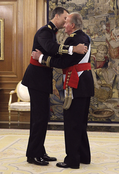 King Juan Carlos places the sash of the captain general of the armed forces on his son King Felipe VI of Spain in a ceremony held in the Hearing Room Zarzuela Palace, prior to the King's official coronation ceremony on June 19, 2014 in Madrid, Spain. The coronation of King Felipe VI is held in Madrid. His father, the former King Juan Carlos of Spain abdicated on June 2nd after a 39 year reign. The new King is joined by his wife Queen Letizia of Spain.