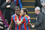 Wilfried Zaha of Crystal Palace celebrates with teammate Yohan Cabaye after scoring his sides first goal during the Premier League match between Crystal Palace and Brighton and Hove Albion at Selhurst Park on April 14, 2018 in London, England.