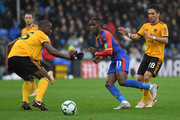 Wilfried Zaha of Crystal Palace is challenged by Willy Boly and Joao Moutinho of Wolverhampton Wanderers during the Premier League match between Crystal Palace and Wolverhampton Wanderers at Selhurst Park on October 6, 2018 in London, United Kingdom.