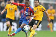 Wilfried Zaha of Crystal Palace battles for possession with Jonny Otto of Wolverhampton Wanderers during the Premier League match between Crystal Palace and Wolverhampton Wanderers at Selhurst Park on October 6, 2018 in London, United Kingdom.