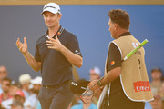 Justin Rose of England reacts with caddie Mark Fulcher on the 18th green during the final round of the DP World Tour Championship at Jumeirah Golf Estates on November 19, 2017 in Dubai, United Arab Emirates.