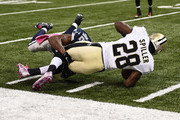 C.J. Spiller #28 of the New Orleans Saints is tackled by  Barry Church #42 of the Dallas Cowboys during the third quarter against the New Orleans Saints at Mercedes-Benz Superdome on October 4, 2015 in New Orleans, Louisiana.