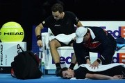 Britain's Jamie Murray receives treatment as Brazil's Bruno Soares rests during a break in play against Croatia's Ivan Dodig and Bosnia-Herzegovina's Marcel Granollers during their men's doubles round-robin match on day four of the ATP World Tour Finals tennis tournament at the O2 Arena in London on November 15, 2017. / AFP PHOTO / Glyn KIRK