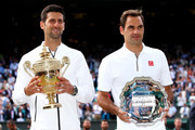 Novak Djokovic of Serbia and Roger Federer of Switzerland pose for a photo with their trophies after Men's Singles final against Roger Federer of Switzerland during Day thirteen of The Championships - Wimbledon 2019 at All England Lawn Tennis and Croquet Club on July 14, 2019 in London, England.