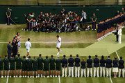 Roger Federer of Switzerland walks past Novak Djokovic of Serbia with his runners-up trophy after the Men's Singles final during Day thirteen of The Championships - Wimbledon 2019 at All England Lawn Tennis and Croquet Club on July 14, 2019 in London, England.