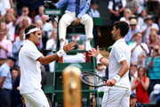 Novak Djokovic of Serbia shakes hands with Roger Federer of Switzerland at the net following victory in his Men's Singles final during Day thirteen of The Championships - Wimbledon 2019 at All England Lawn Tennis and Croquet Club on July 14, 2019 in London, England.