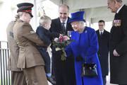 """Britain's Queen Elizabeth II receives a bouquet of flowers from two year old Alfie Lun as she arrives to unveil The Iraq and Afghanistan memorial at Victoria Embankment Gardens in central London on March 9, 2017..The preceding """"Service of Dedication"""" honoured the service and duty of both the UK Armed Forces and civilians in the Gulf region, Iraq and Afghanistan, and those who supported them back home, from 1990-2015 / AFP PHOTO / POOL / Toby Melville"""