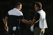 Justin Rose of England shakes hands with caddie Mark Fulcher after finishing on the 18th green during the first round of the Dell Technologies Championship at TPC Boston on August 31, 2018 in Norton, Massachusetts.