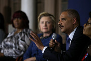Democratic presidential candidate former Secretary of State Hillary Clinton (C) looks on as former attorney general Eric Holder speaks during a panel discussion on gun violence at St. Paul's Baptist Church on April 20, 2016 in Philadelphia, Pennsylvania. Hillary Clinton and former attorney general Eric Holder held a panel discussion with parents of victims of gun and police violence.