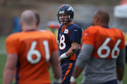 Quarterback Peyton Manning #18 of the Denver Broncos takes part in practice with center Matt Paradis #61 of the Denver Broncos and center Manny Ramirez #66 of the Denver Broncos at the Paul D. Bowlen Memorial Broncos Centre on August 5, 2014 in Englewood, Colorado.