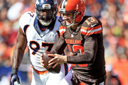 Quarterback Josh McCown #13 of the Cleveland Browns is pressured by defensive end Malik Jackson #97 of the Denver Broncos during the second quarter at Cleveland Browns Stadium on October 18, 2015 in Cleveland, Ohio.