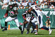 Chris Ivory #33 of the New York Jets runs around Terrance Knighton #98 and Corey Nelson #52 of the Denver Broncos in the second quarter at MetLife Stadium on October 12, 2014 in East Rutherford, New Jersey.