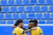 Lionel Messi of FC Barcelona celebrates with his teammate Arturo Vidal after scoring his sides fifth goal during the Liga match between Deportivo Alaves and FC Barcelona at Estadio de Mendizorroza on July 19, 2020 in Vitoria-Gasteiz, Spain. Football Stadiums around Europe remain empty due to the Coronavirus Pandemic as Government social distancing laws prohibit fans inside venues resulting in all fixtures being played behind closed doors.