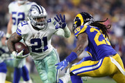 Ezekiel Elliott #21 of the Dallas Cowboys runs with the ball against Mark Barron #26 of the Los Angeles Rams in the fourth quarter in the NFC Divisional Playoff game at Los Angeles Memorial Coliseum on January 12, 2019 in Los Angeles, California.