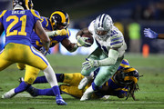 Ezekiel Elliott #21 of the Dallas Cowboys is tackled by Mark Barron #26 of the Los Angeles Rams in the fourth quarter in the NFC Divisional Playoff game at Los Angeles Memorial Coliseum on January 12, 2019 in Los Angeles, California.