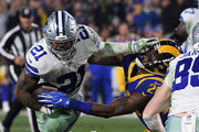 Ezekiel Elliott #21 of the Dallas Cowboys stiff arms Mark Barron #26 of the Los Angeles Rams in the fourth quarter in the NFC Divisional Playoff game at Los Angeles Memorial Coliseum on January 12, 2019 in Los Angeles, California.