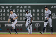 (L-R) Brett Gardner #11, Andrew McCutchen #26, Aaron Judge #99 of the New York Yankees walk toward their teammates after their 6-2 win in Game Two of the American League Division Series against the Boston Red Sox at Fenway Park on October 6, 2018 in Boston, Massachusetts. The Yankees defeated the Red Boston Red Sox 6-2.