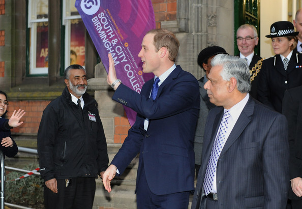 Prince William, Duke of Cambridge waves as he leaves alongside Councillor Mahmood Hussain (R) from Birmingham City Council after his visit to South and City College on November 29, 2013 in Birmingham, England.