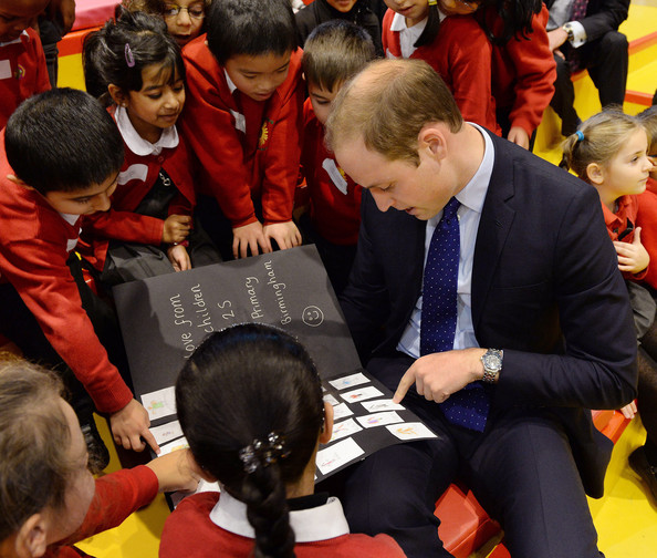 Prince William, Duke of Cambridge looks at a card made by the young children from Chandos Primary School during story time as he visits Birmingham Library on November 29, 2013 in Birmingham, England.