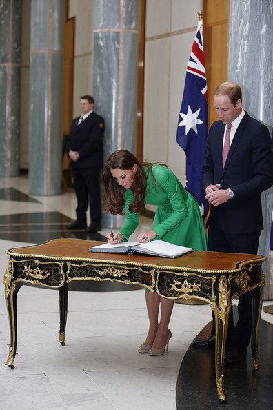 Catherine, the Duchess of Cambridge and Prince William, Duke of Cambridge sign the Prime Minister's and Presiding Officer's Visitors books on the Queen Victoria Writing Table in the Marble Foyer at Parliament House on April 24, 2014 in Canberra, Australia. The Duke and Duchess of Cambridge are on a three-week tour of Australia and New Zealand, the first official trip overseas with their son, Prince George of Cambridge.