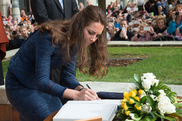 Catherine, Duchess of Cambridge signs the Visitor's Book during a walk about in Civic Square on April 16, 2014 in Wellington, New Zealand. The Duke and Duchess of Cambridge are on a three-week tour of Australia and New Zealand, the first official trip overseas with their son, Prince George of Cambridge.
